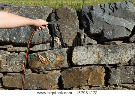 Caucasian hand holding a stripped hose and sprinkling water. Natural stones on the background