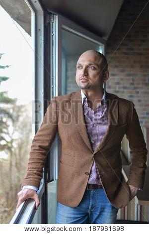 Handsome indian businessman, standing near panoramic window
