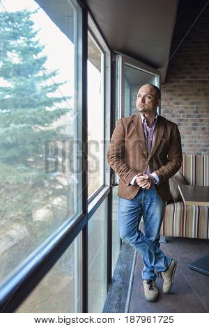 Handsome indian businessman, standing near panoramic window, full length shot.