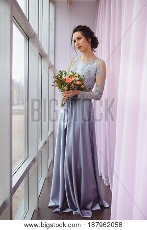 Beautiful woman in a plum dress posing with a bouquet of roses near window.