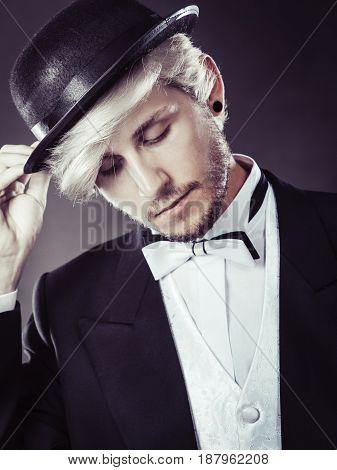 Tuxedo male fashion classical look concept. Elegantly dressed man wearing black fedora hat. Studio shot on dark background