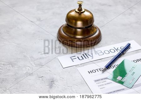 hotel reservation blank and ring on stone desk background