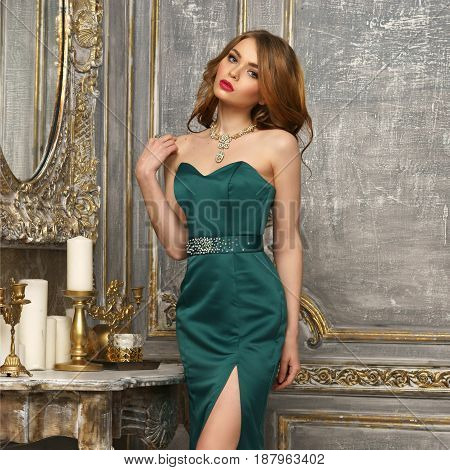 Elegant red hair girl with curls in green mermaid gress sitting on table in luxury interior and looking away. Fashion style portrait