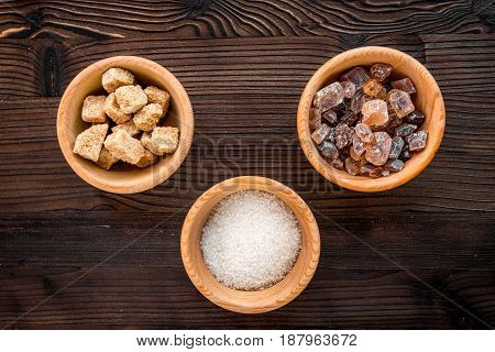 lumps of sugar with bowls sweet set on wooden kitchen table background top view