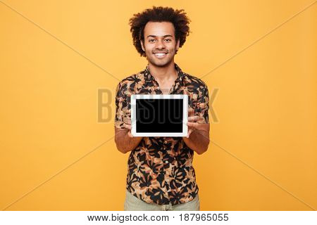 Portrait of a young happy afro american man showing blank screen pc tablet isolated over yellow background
