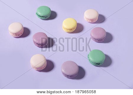 Picture of a lot of sweet colorful macaroons on purple table background.