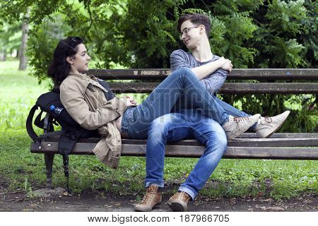Lovely Young Couple, Boy And Girl Sitting On A Park Bench Talking, Enjoy And Have Great Fun