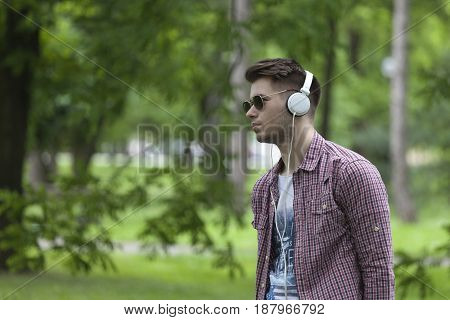 Portrait of a young man standing in the park and listening to music. Relax and enjoy.