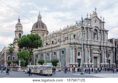 Locals and tourists gather around Roman Catholic Cathedral (Duomo) dedicated to Saint Agatha on the main square - Catania Sicily Italy 16 October 2011