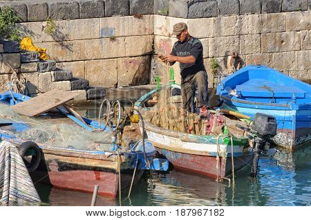 Fisherman tries to untangle his net in the port - Siracusa Sicily Italy, 17 October 2011