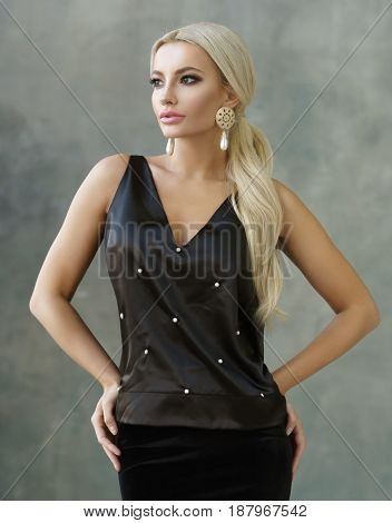 Fashion portrait of stylish blonde girl wearing black skirt and blouse. Woman with ponytail hair wearing earrings