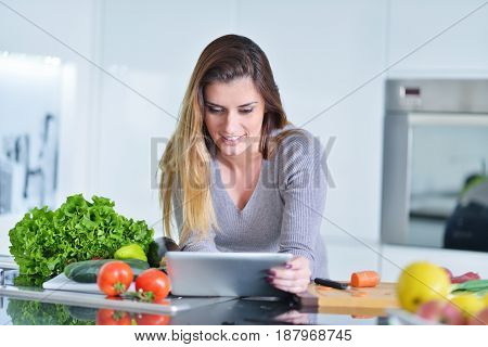 Young woman is making online shopping by tablet computer. Housewife found new recipe for cooking in a kitchen.