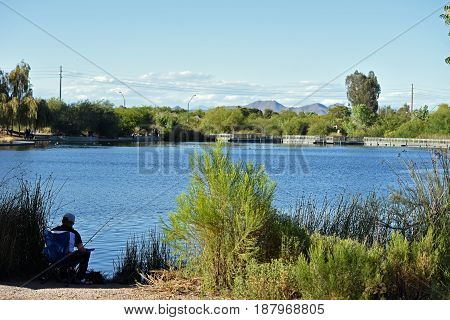 Riparian Preserve Park, Gilbert, AZ, circa may 2017. Man fishing at the main pond.