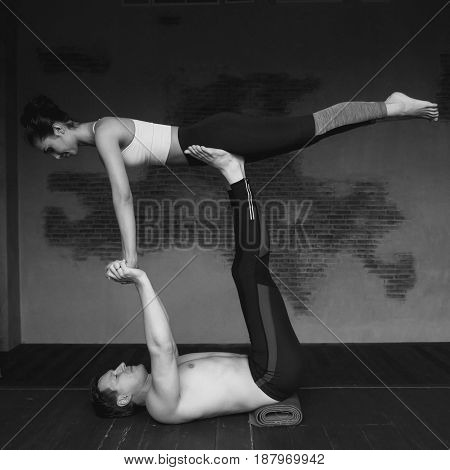 Young caucasian couple practice acroyoga in loft interior. Sporty handsome man supporting and holding slim beautiful brunette woman. Acro yoga concept showing strength and trust