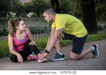 Man helps woman with injured knee at sport activity.