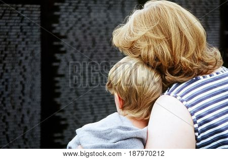 OCT 27, 2006. SEATTLE, WA. CIRCA: Mother and son looking for family members names on the wall for military soldiers who died for their country.