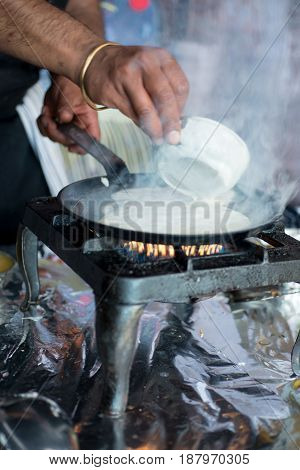Hands Pouring Mixture To Make Dosa Onto Hot Pan