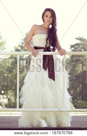 outdoor portrait of young wonderful bride standing in summer park