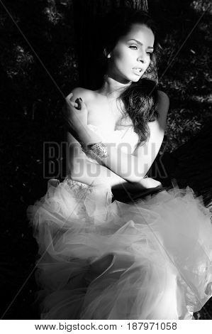 monochrome fashion portrait of young beautiful tender woman in white dress lying on the tree and looking away