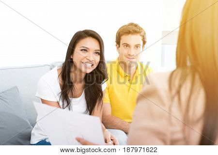 Young interracial couple meeting with consultant (or counselor financial adviser real estate agent etc.)