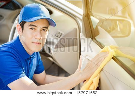Auto service staff cleaning car door - car detailing and valeting concept