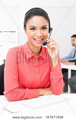 Asian businesswoman wearing microphone headset in the office - call center and telemarketer concept