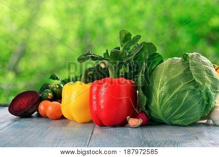 Different raw fresh vegetables оn blue rustic wooden table cloe up. Vegetables background