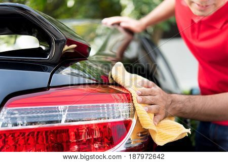 A man cleaning car tail light - auto service detailing and valeting concept