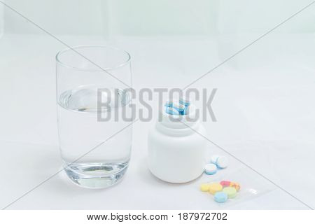 Medicines with drinking water on white background
