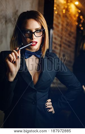 Young attractive girl in a jacket bow tie and glasses. Femme fatale. Evening makeup smokey eye. She lustfully bites the pen.