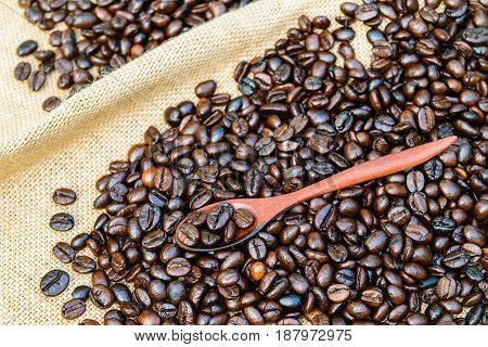 Roasted coffee beans with wooden spoon on a sack