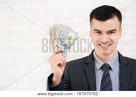 Young smiling businessman showing US dollar money