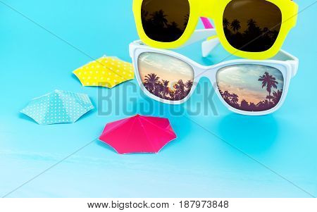 colorful sunglasses and parasol at light blue studio background with palm tree reflection on glassSummer vacation concept.