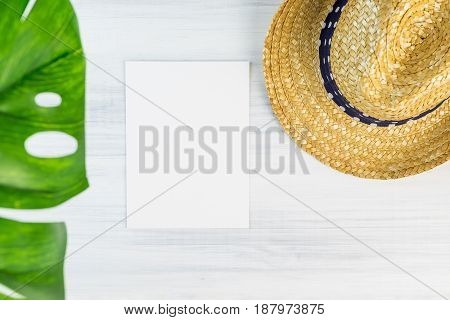 Blank White Paper Card On Wood Table Top View With Straw Hat And Blur Foreground Tropical Palm Leaf