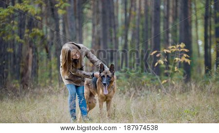 Young girl walking with dog in autumn forest