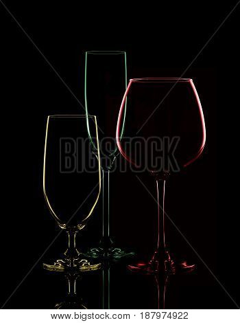 Colored transparent glasses for wine on a black background.