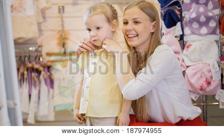 Shopping for kids - Mom straightens the beads of her little daughter in front of the mirror