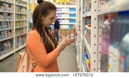 A girl buys mineral water in a store