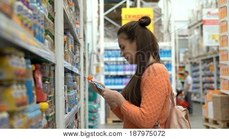 Young mom buys baby food in supermarket.