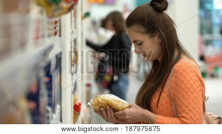 Woman buys macaroni in a store or supermarket