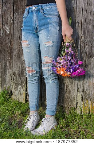 teenage girl wearing frayed blue jeans and sneakers holding a colorful daisy bouquet by old wooden barn