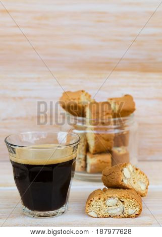 Homemade biscotti cantuccini or cantucci Italian almond sweets biscuits (cookies) and glass of espresso coffee on wooden table.