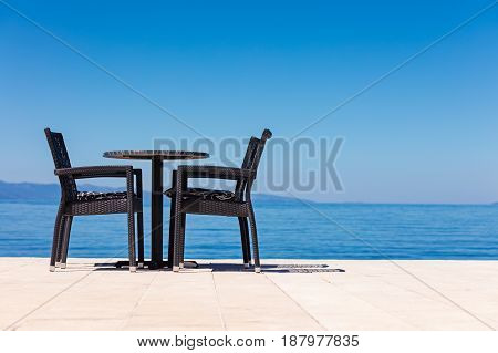 background of two chairs and beach and small bag and table place.