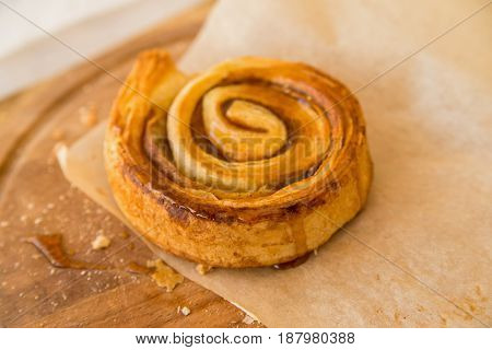 Close up freshly backed cinnamon roll lying on paper