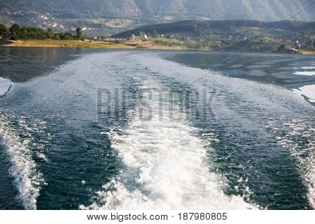 Stormy trace of motor boat crossing the emerald waters