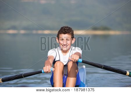 A Young single scull rowing competitor paddles on the tranquil lake.