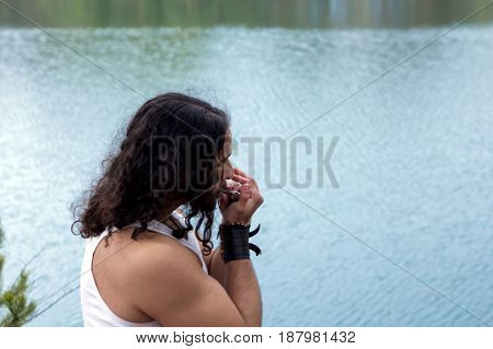 Young man plays on a harmonica on the river bank. Relax by the river.