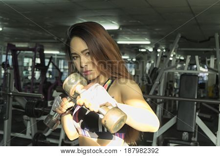 Fitness woman in training showing exercises with dumbbells in gym soft focus