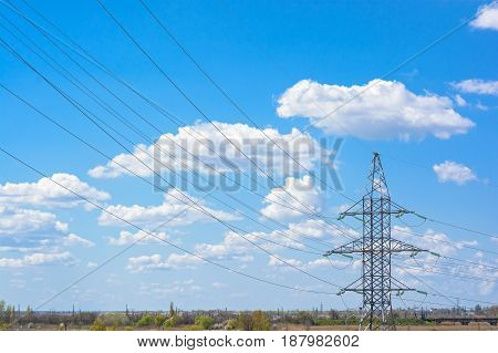 Electricity pylons with wires against blue sky