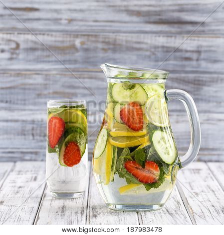 Dietary detox drink with lemon juice red strawberry cucumber and mint leaves in clear water with ice.